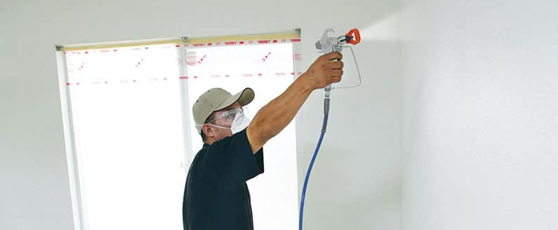 man-spraying-wall-with-airless-sprayer