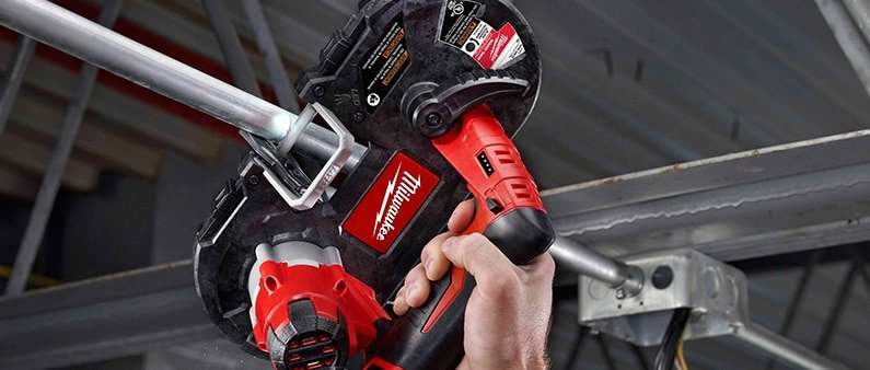 A Man Cutting Metal Pipe With Milwaukee 2429-21XC