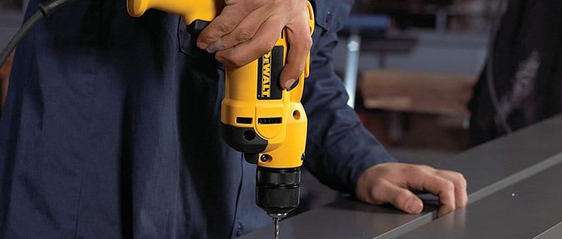 Man Using DeWalt DWD112 To Drill Hole