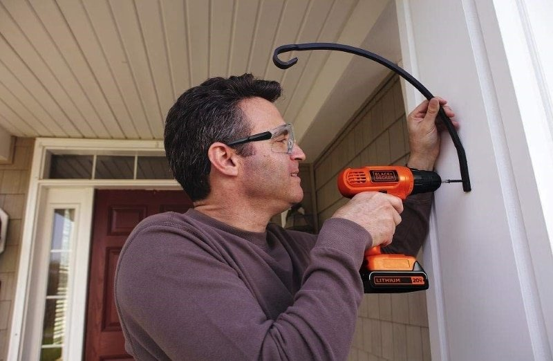 A man working with Black and Decker BDC120VA100 Drill