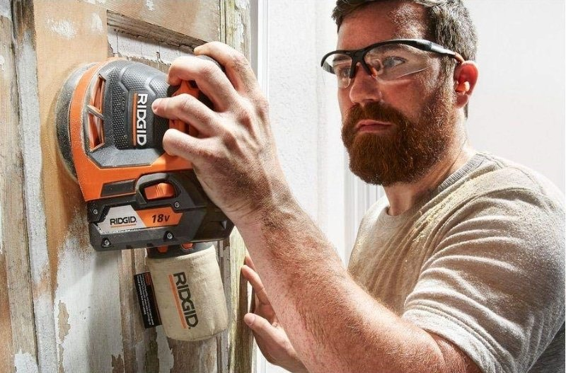 A man working with Ridgid R8606B GEN5X Orbbit Sander